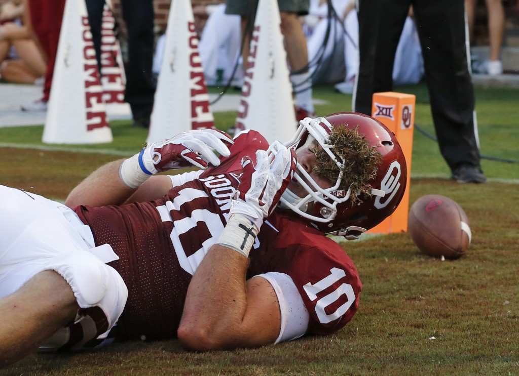 Oklahoma tight end Blake Bell (10) comes up with turf stuck in his helmet during the second quarter of an NCAA college football game against Louisiana Tech in Norman, Okla., Saturday, Aug. 30, 2014. (AP Photo/Sue Ogrocki)